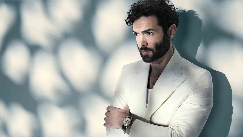 Ethan Peck of Star Trek Discovery in a white jacket and tank top