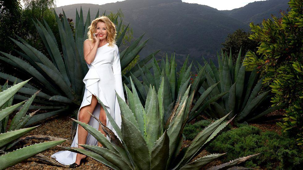 Melody Thomas Scott in a white wraparound dress amidst cactii.