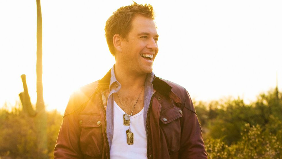 Michael Weatherly of Bull in brown bomber jacket and dog tags
