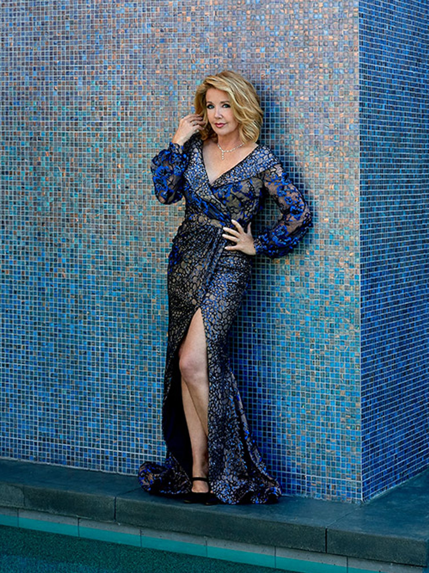 Melody Thomas Scott in a long textured blue dress against a blue mosaic tile wall.