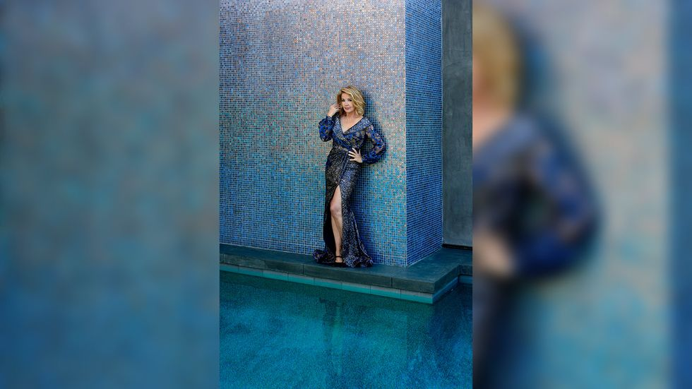Melody Thomas Scott of The Young and the Restless in a blue beaded gown against a blue tiled wall