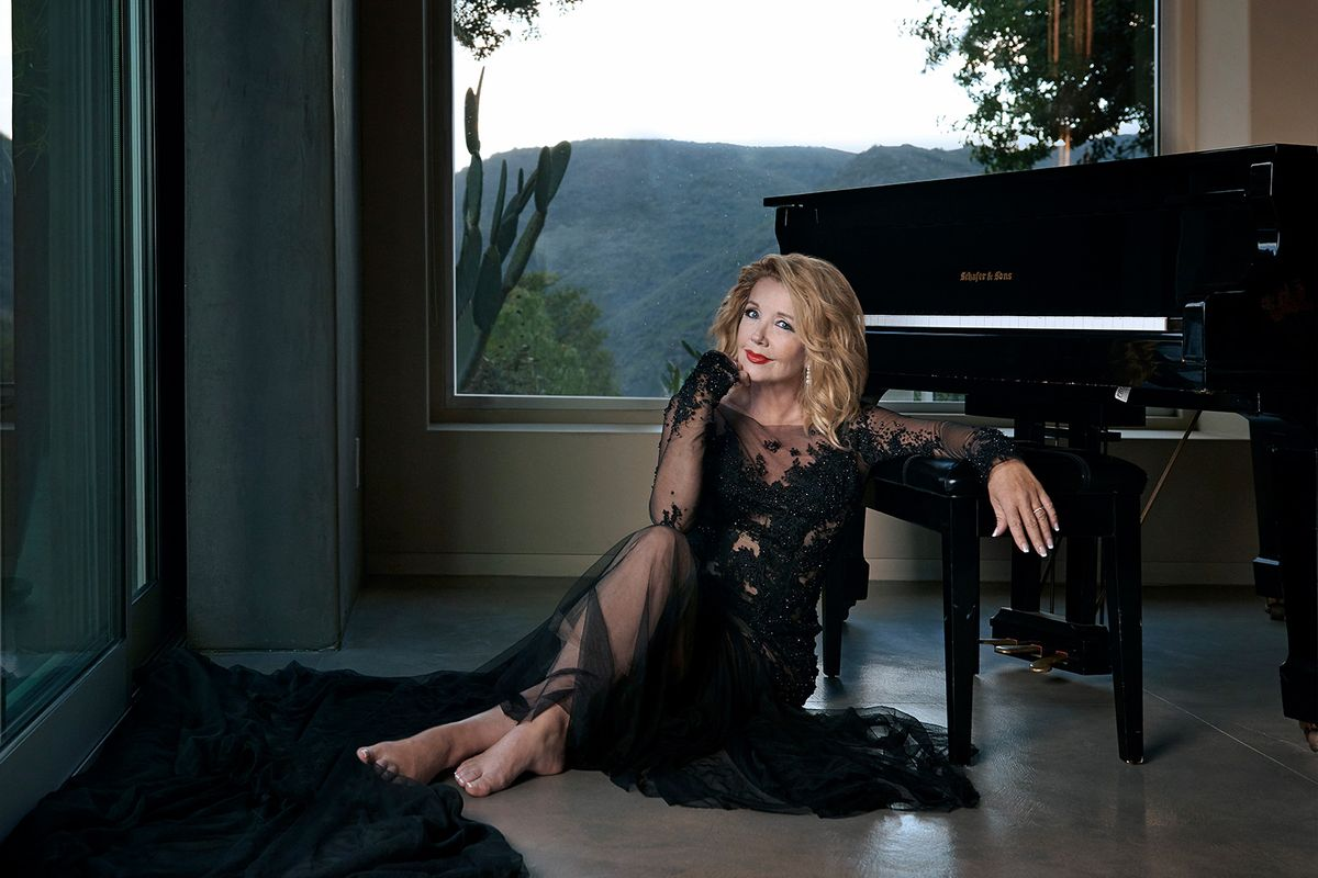 Melody Thomas Scott in a lacy black dress up against a piano.