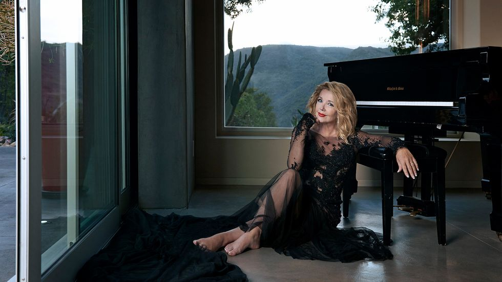Melody Thomas Scott of The Young and the Restless in a sheer black gown next to a piano