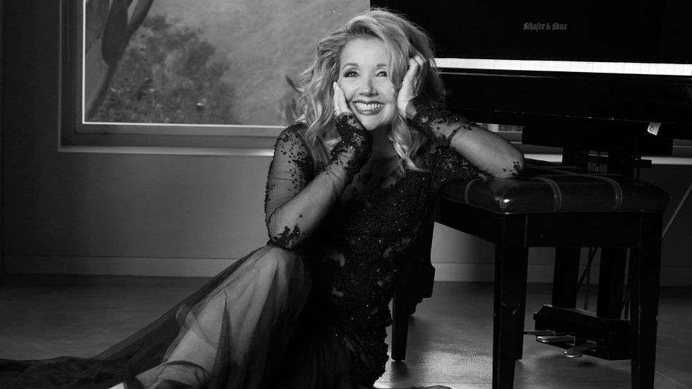 Melody Thomas Scott of The Young and the Restless leaning on a piano bench