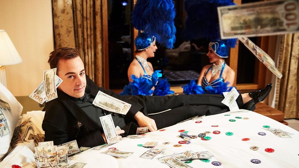 Sean Murray surrounded by money and poker chips in black outfit