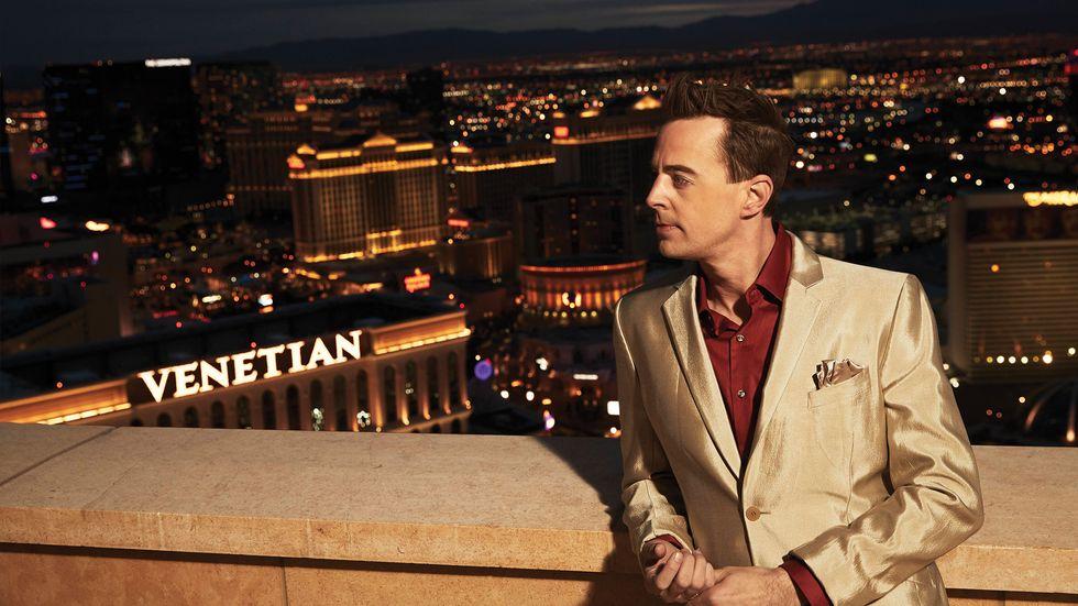 Sean Murray in gold jacket and red button down in front of Las Vegas skyline
