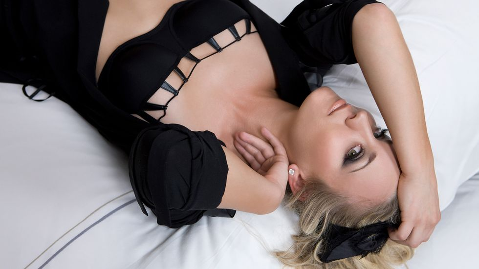 Kaley Cuoco of The Big Bang Theory in black dress on white sheets