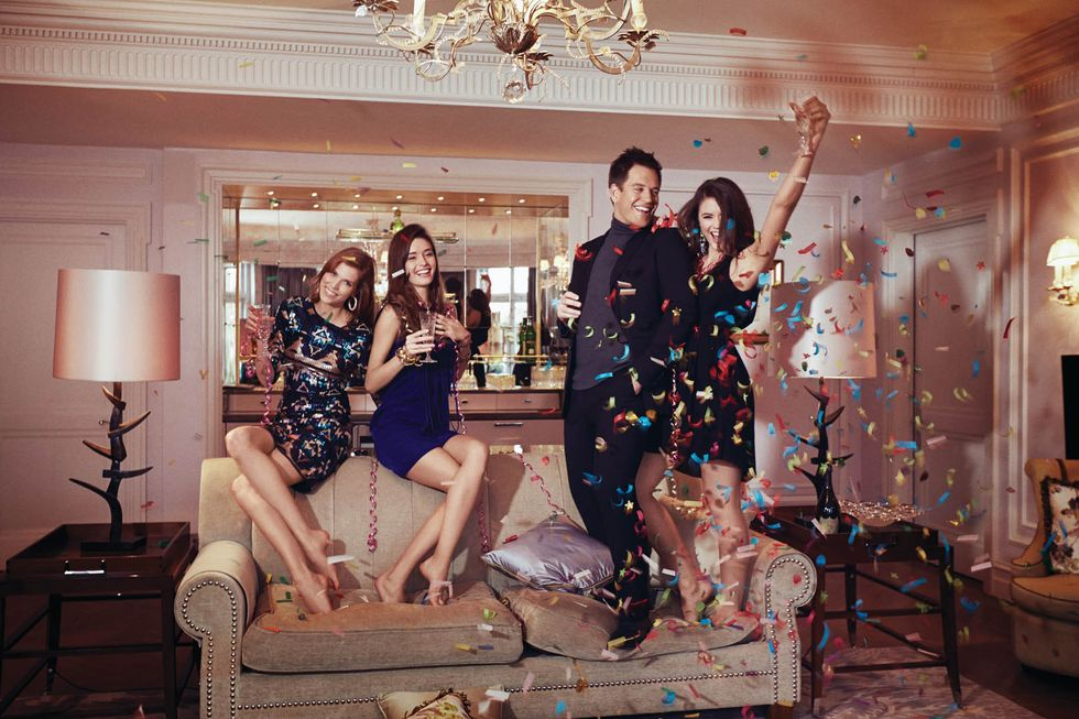 Michael Weatherly standing on a couch with women and confetti