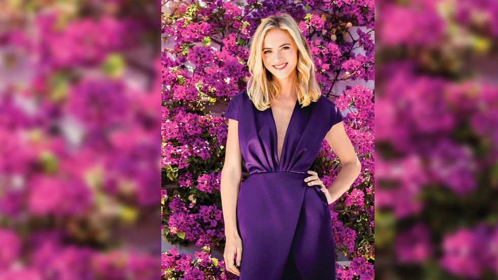 Emily Wickersham in a plunging purple dress as she stands in front of vines of purple Bougainvilleas