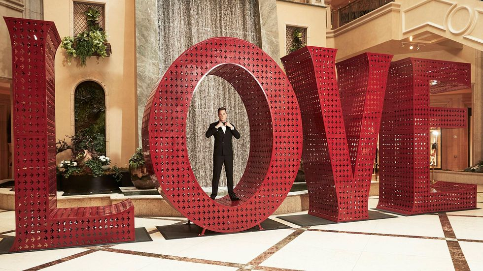 Sean Murray in a suit standing inside of the O of a large three dimensional display that spells out LOVE