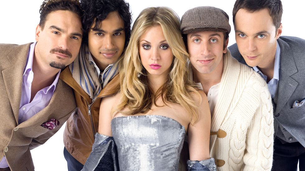 Kaley Cuoco in silver dress surrounded by men of The Big Bang Theory