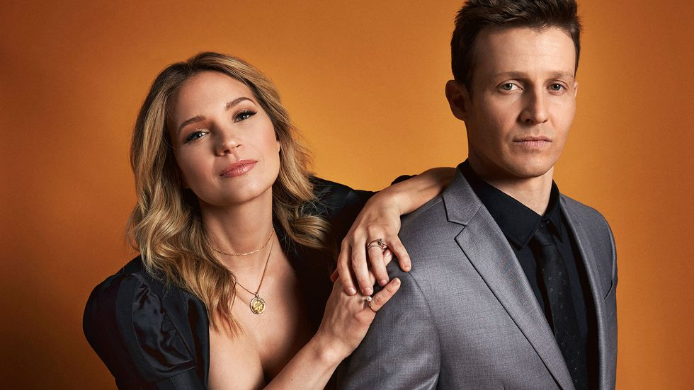 Vanessa Ray and Will Estes against a burnt orange background