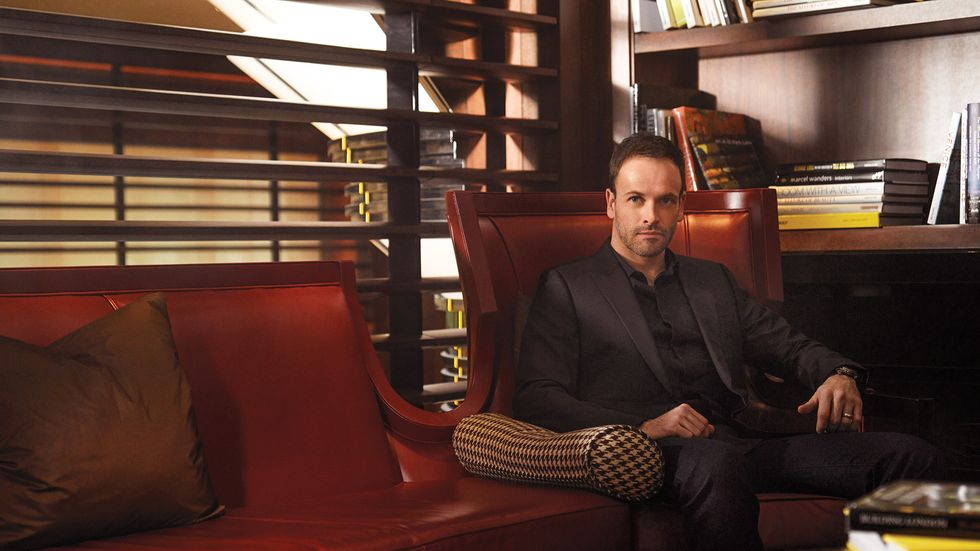 Jonny Lee Miller of Elementary in black on black suit seated in brown leather chair