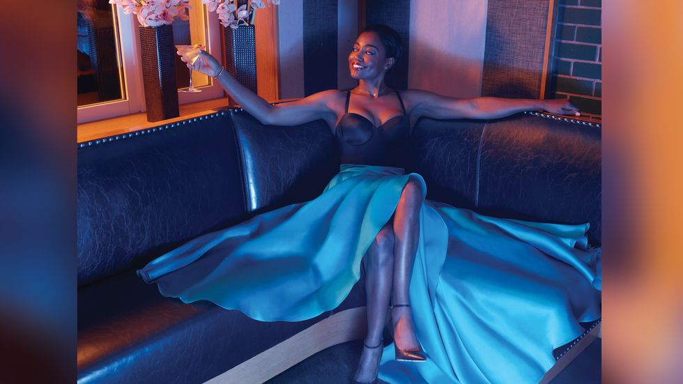 Patina Miller of Madam Secretary in black bodysuit and blue satin skirt sitting in banquette
