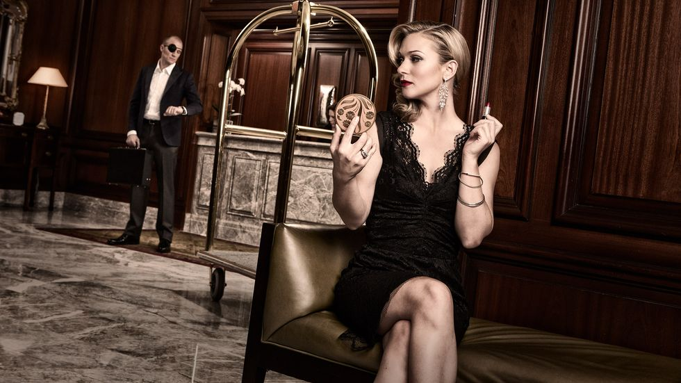 AJ Cook of Criminal Minds in black lace cocktail dress seated in hotel lobby