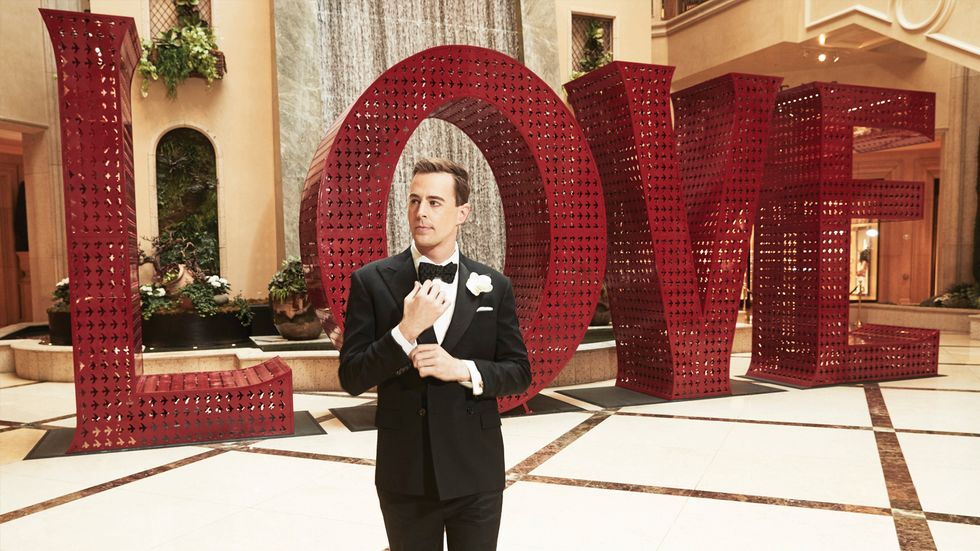 Sean Murray of NCIS in tuxedo in front of waterfall and LOVE sign in Las Vegas