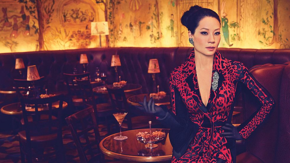 Lucy Liu of Elementary in red and black gown with black gloves and Lorraine Schwartz jewelry