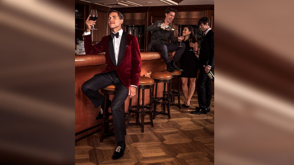 Brian Dietzen of NCIS in red velvet jacket with black satin lapels drinking red wine at bar