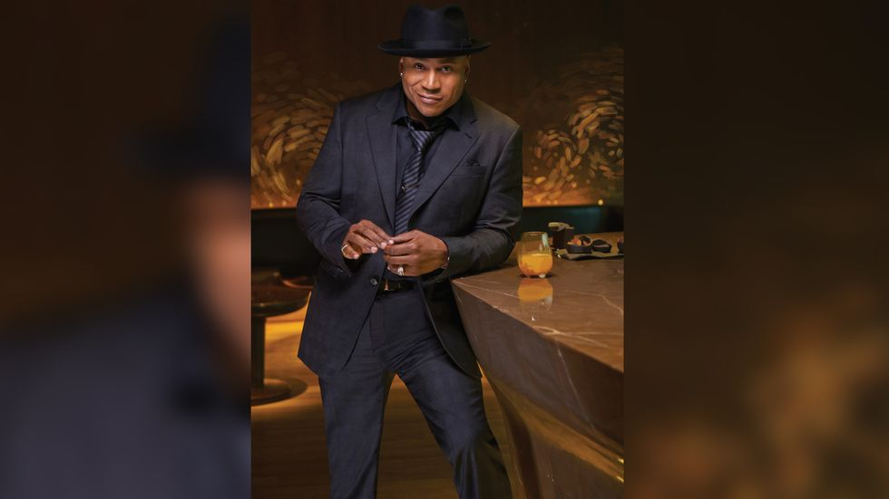 LL COOL J of NCIS Los Angeles in black suit with black shirt and tie and black fedora