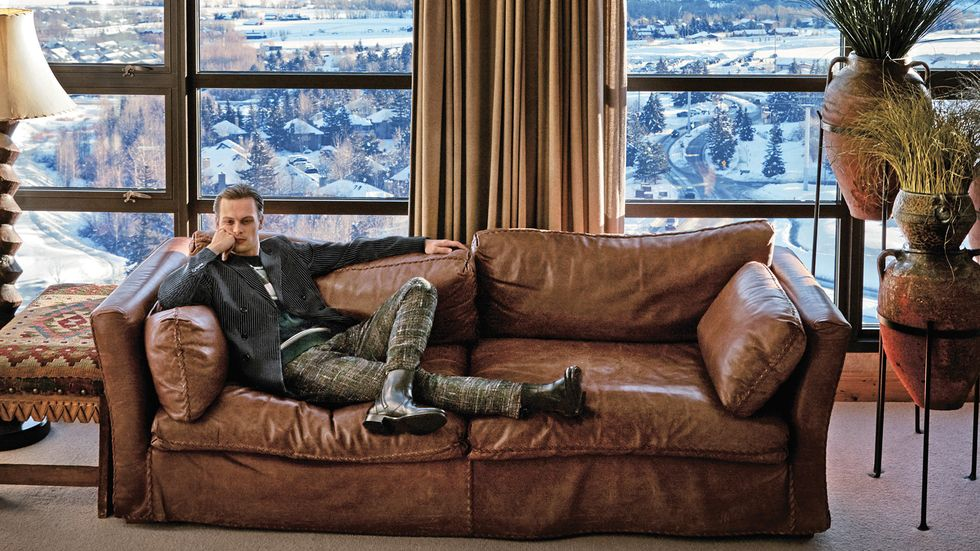 Matthew Gray Gubler of Criminal Minds in tweed pants and jacket on weathered leather sofa