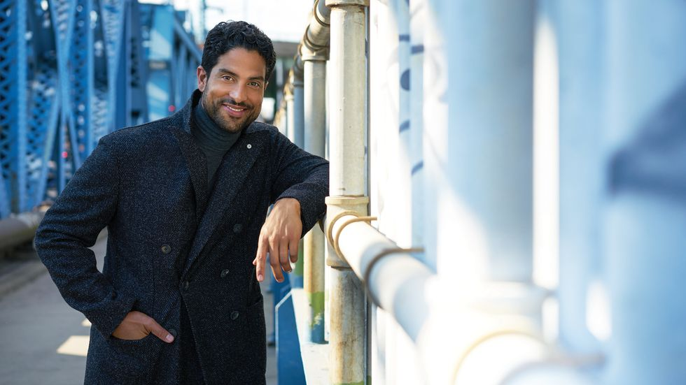 Adam Rodriguez of Criminal Minds in a turtleneck and gray flecked coat on a bridge