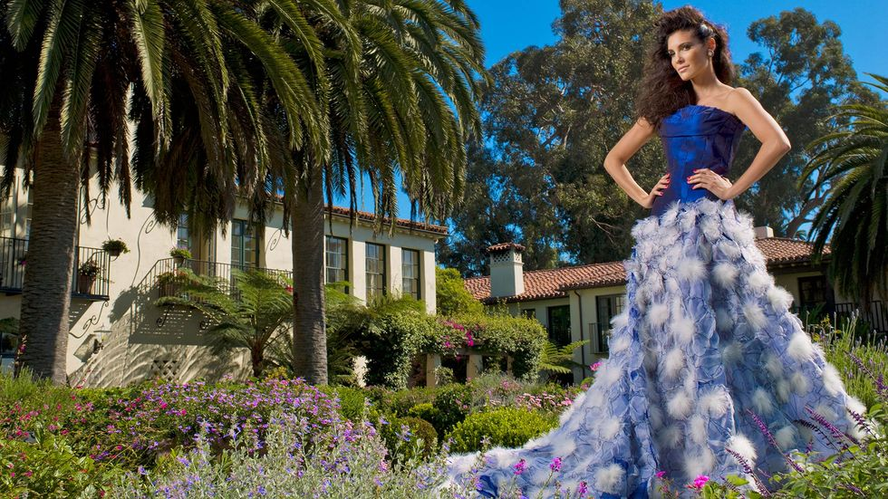 Daniela Ruah of NCIS Los Angeles in blue satin strapless gown with floral skirt in outdoor garden