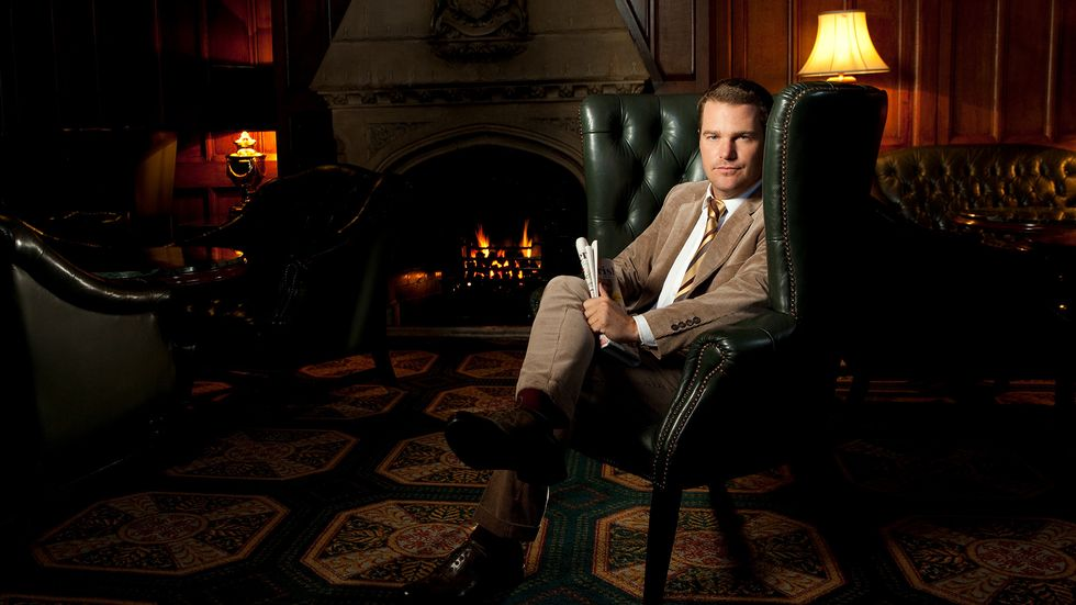 Chris ODonnell of NCIS Los Angeles in brown suit seated in leather chair with fireplace