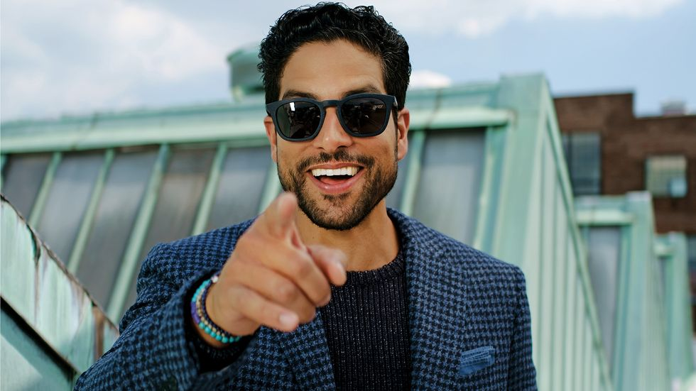 Adam Rodriguez of Criminal Minds in blue houndstooth jacket and sweater and sunglasses