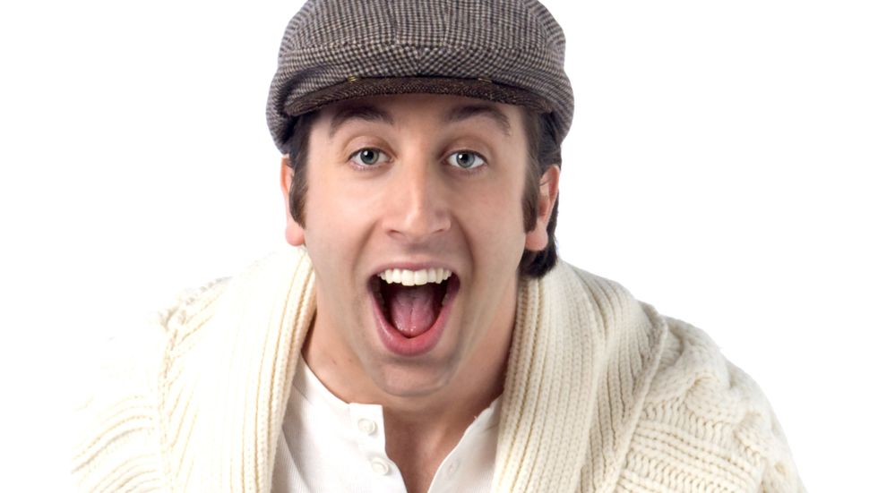 Simon Helberg of The Big Bang Theory in a newsboy cap and a cable knit cardigan
