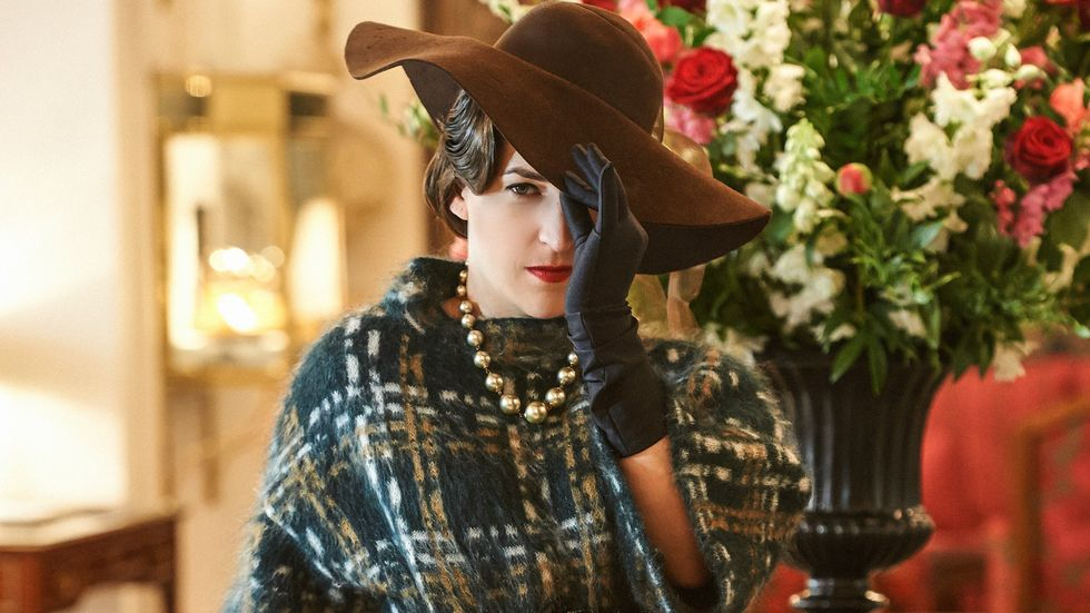 Mayim Bialik of The Big Bang Theory in a floppy hat and a plaid wool wrap