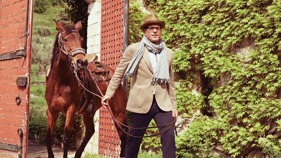 Michael Weatherly of Bull wrapped in a scarf leading a horse from a stable
