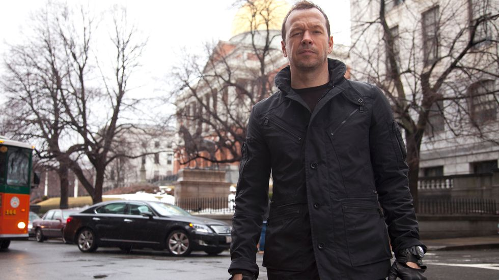 Donnie Wahlberg of Blue Bloods in a black jacket and gloves on the Boston streets