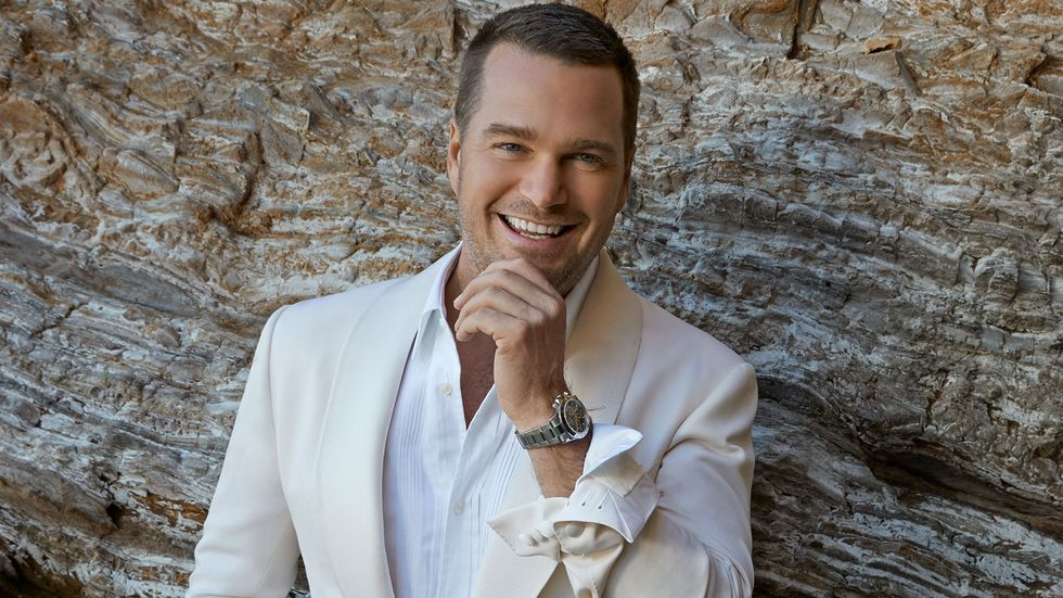 Chris O Donnell of NCIS Los Angeles in white suit up against rocks