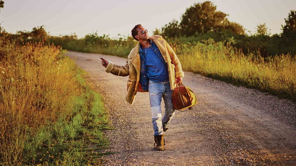Thomas Sadoski of Life in Pieces in jeans and a shearling coat walking on a gravel road