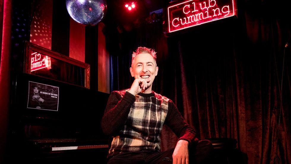 Alan Cumming of Instinct in plaid sweater under disco ball at Club Cumming
