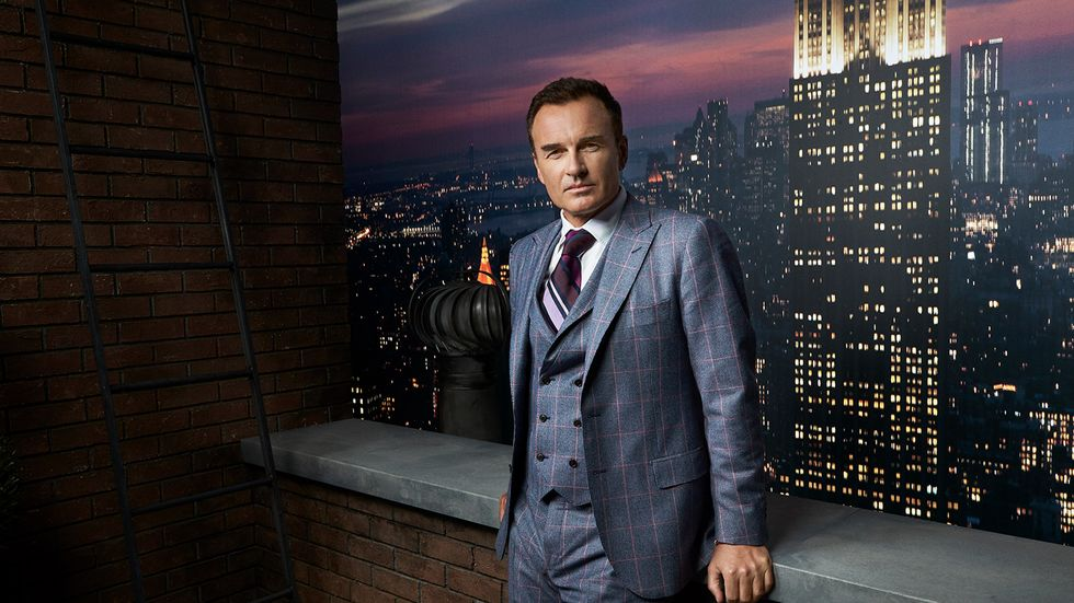 Julian McMahon in checkered suit in front of Empire State Building