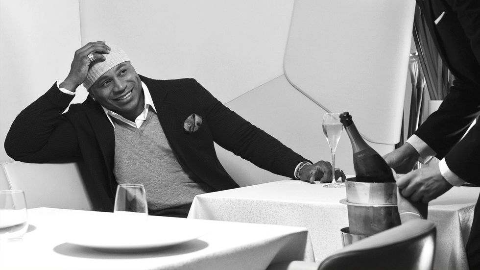 A black and white image of LL COOL J receiving bottle service at a restaurant