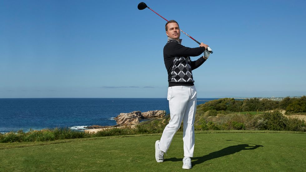 Chris O'Donnell in white pants and a dark patterned sweater hitting a golf ball