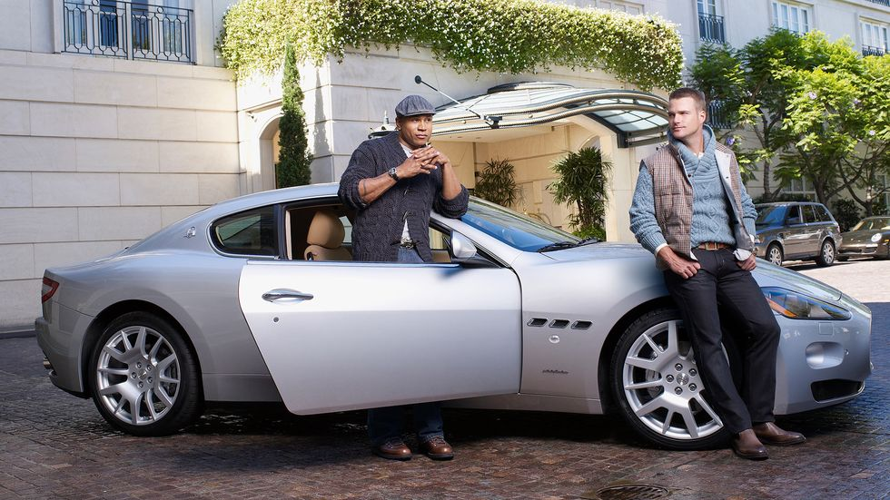 LL COOL J standing by the passenger seat and Chris O Donnell standing by the hood of a silver car