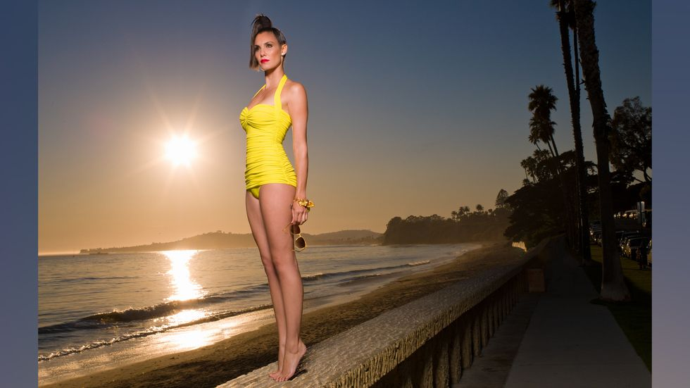 Daniela Ruah in a yellow one piece bathing suit standing on her toes near the water