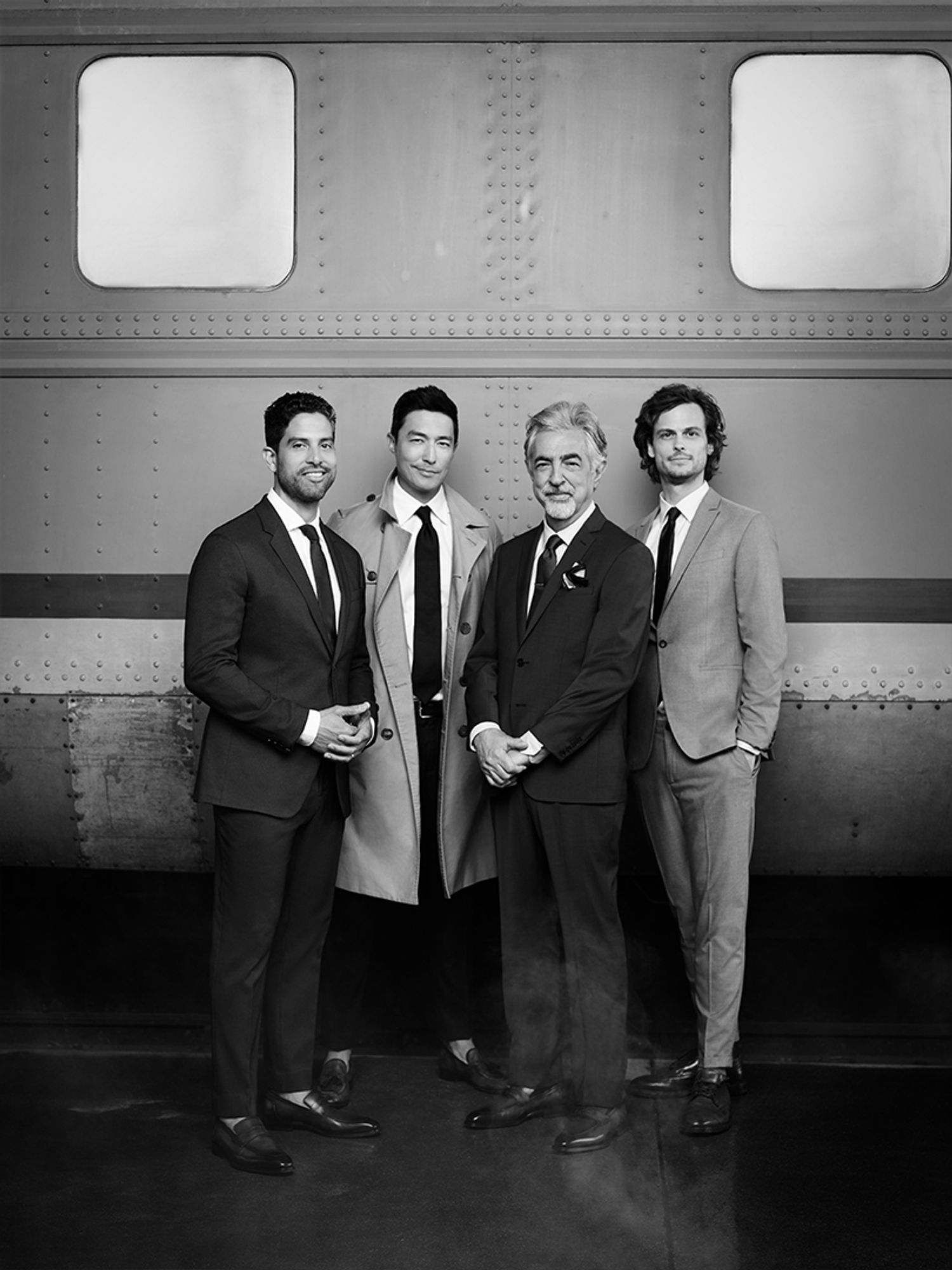 group of men wearing suits in front of train black and white