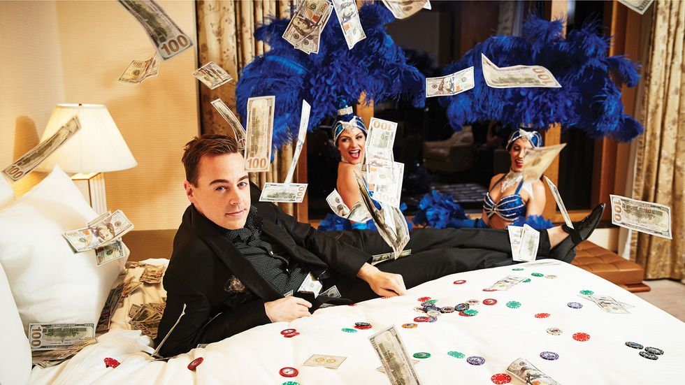 Sean Murray in Vegas on bed with money and poker chips