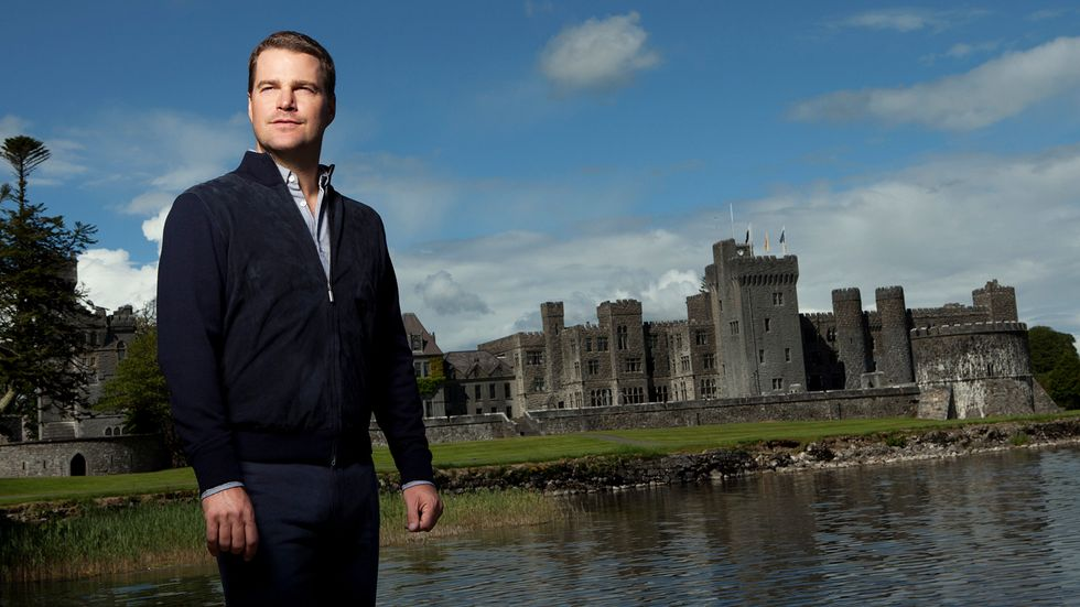 Chris ODonnell in black outfit in front of a castle in Ireland