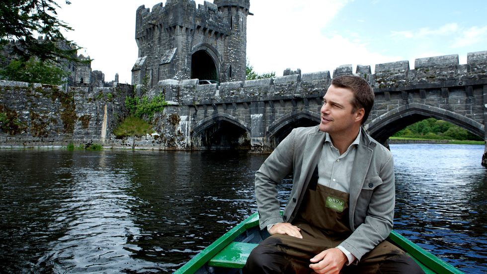 Chris ODonnell in a boat in front of a castle's bridge in Ireland
