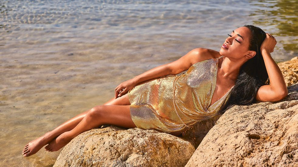 Candice Patton lounging on rocks in sparkly gold dress