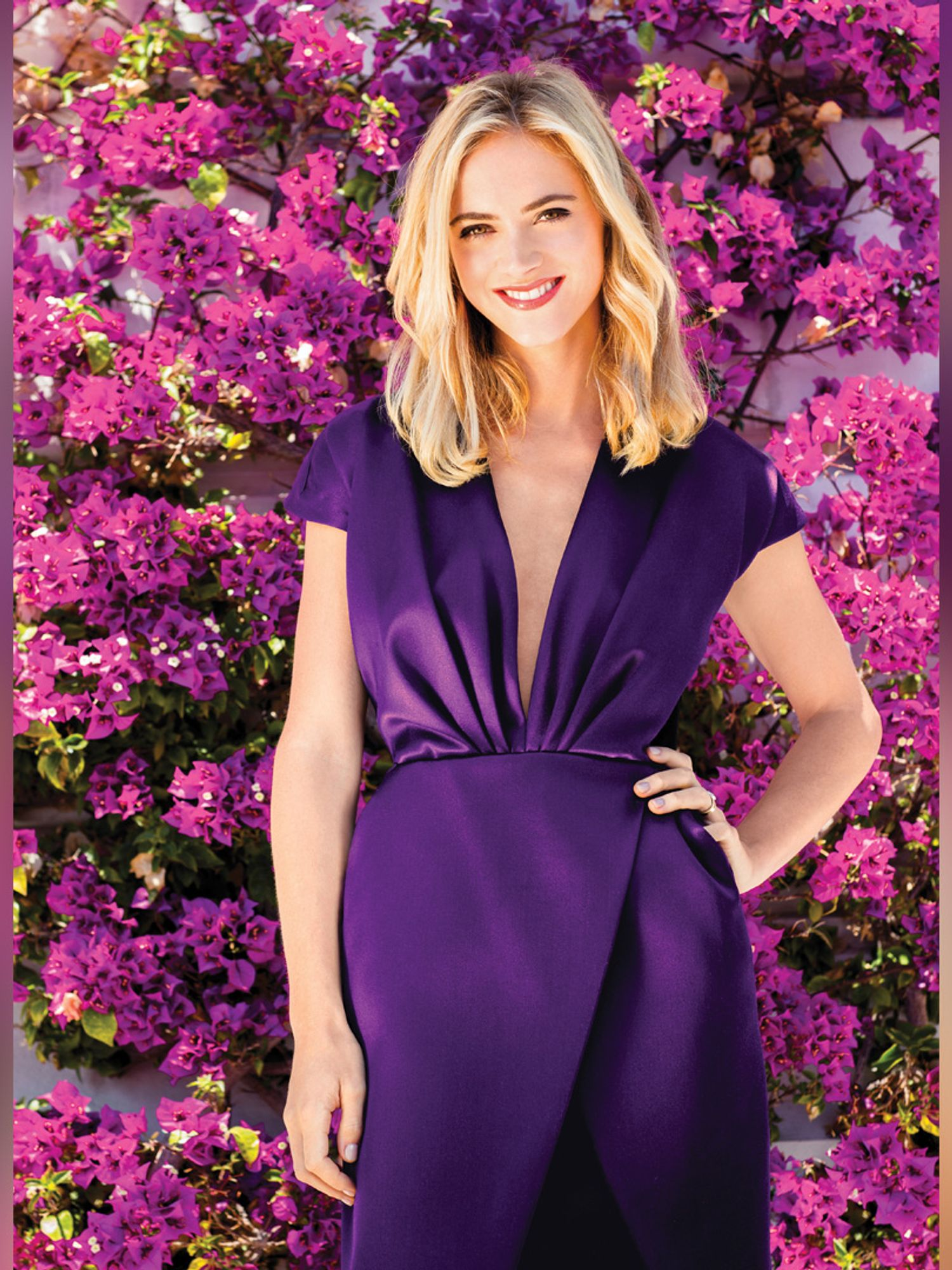 Emily Wickersham of NCIS in violet dress in front of flowers