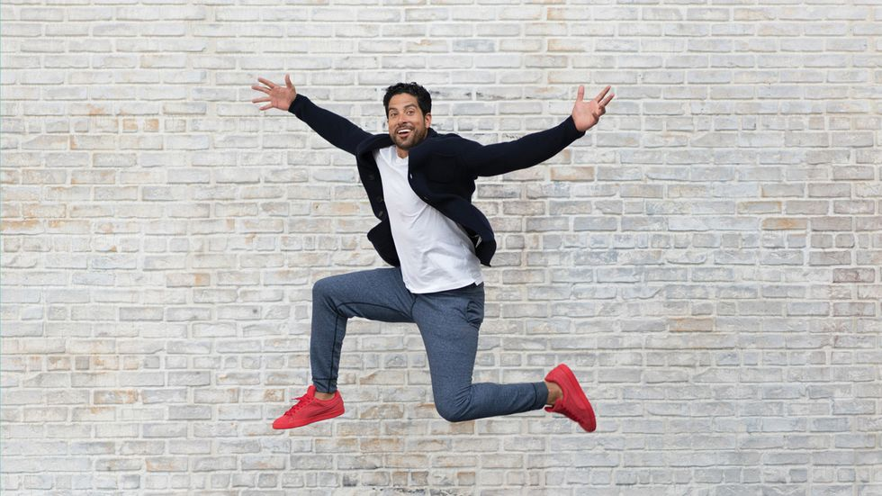 Adam Rodriguez of Criminal Minds jumping in front of a brick wall