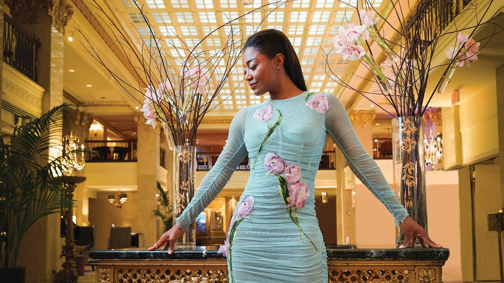 Patina Miller of Madam Secretary wearing a flower trimmed dress in front of vases