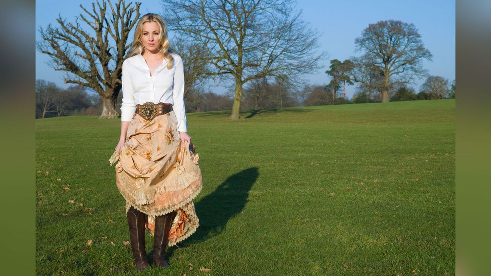 Kaley Cuoco of The Big Bang Theory in a prairie skirt and boots on a grassy knoll