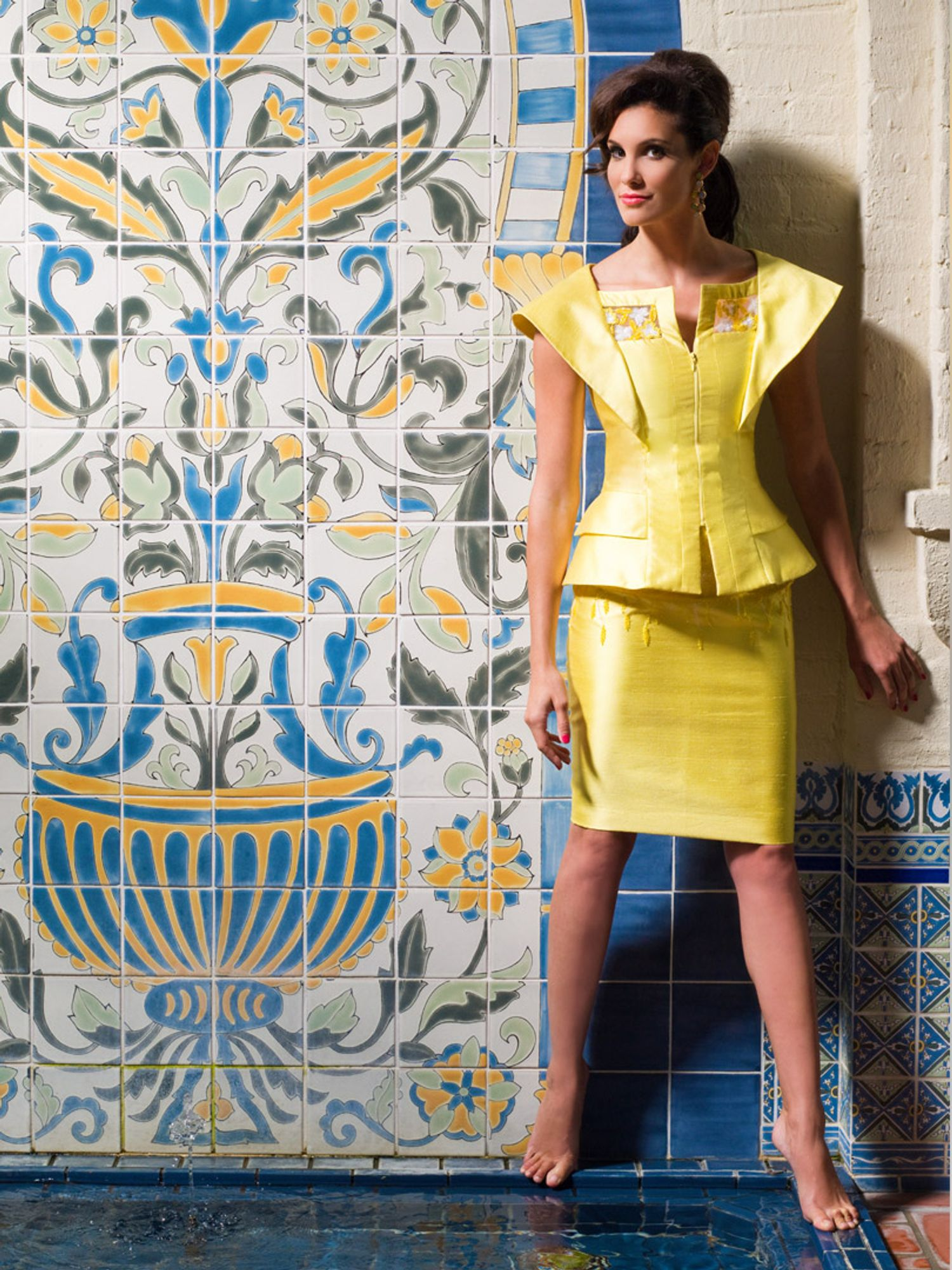 Daniela Ruah of NCIS Los Angeles in a yellow dress against blue and yellow tile